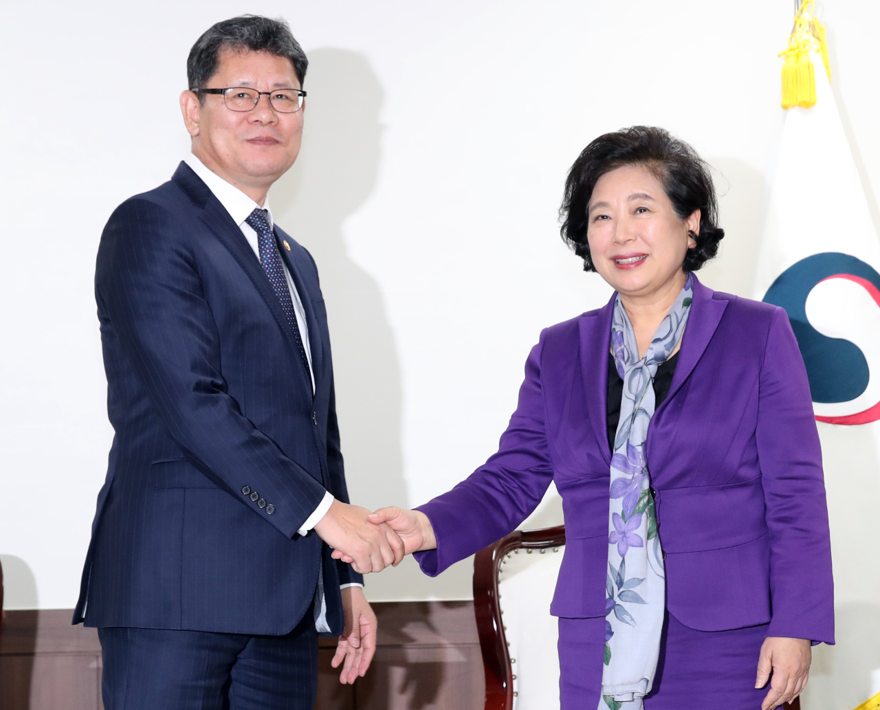 South Korean Unification Minister Kim Yeon-chul (left) shakes hands with Hyundai Group Chairwoman Hyun Jeong-eun at the ministry in Seoul, Thursday. (Yonhap)