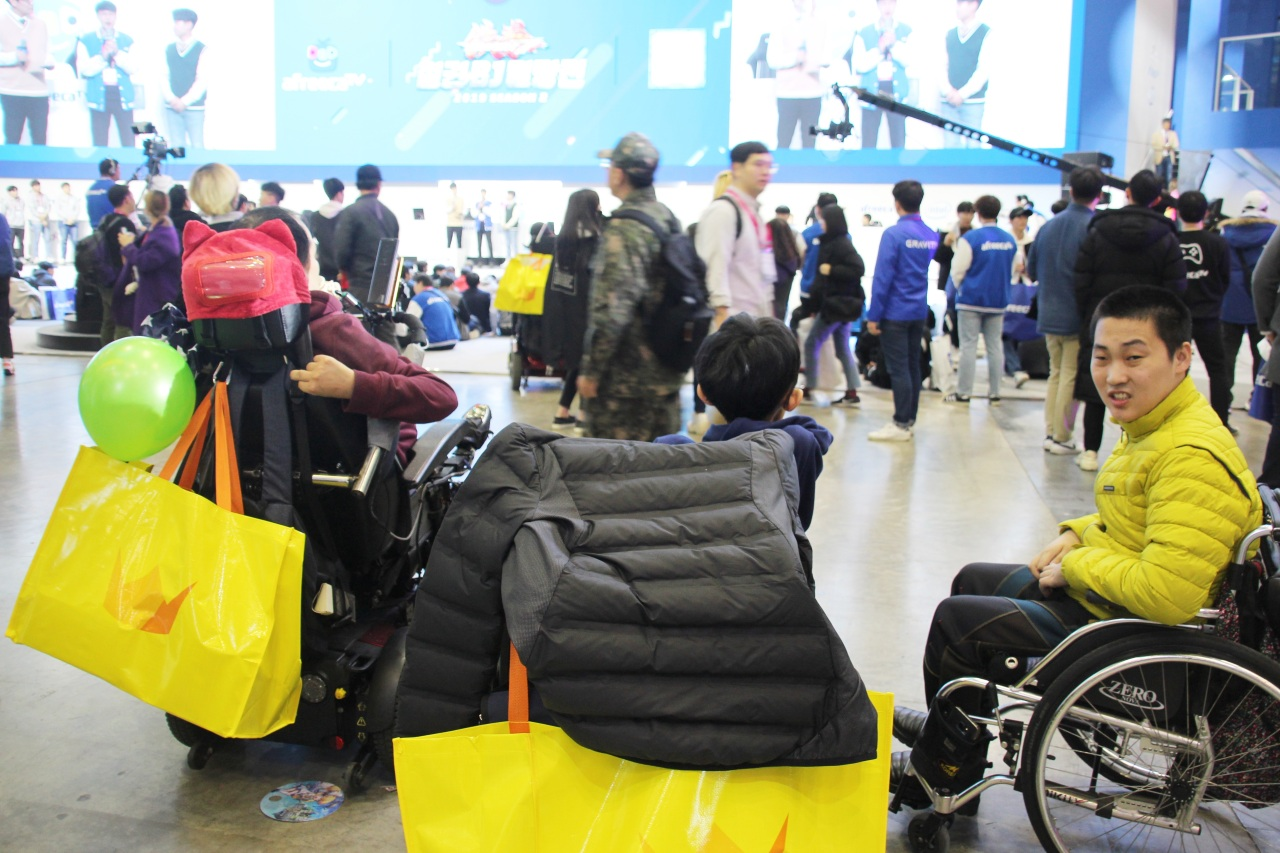 Visitors on wheelchairs watch live esports at G-Star 2019. (Lim Jeong-yeo/The Korea Herald)