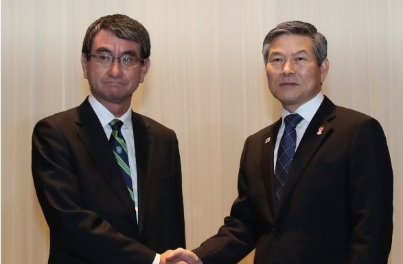 South Korean Defense Minister Jeong Kyeong-doo and Japanese Defense Minister Taro Kono hold hands in their bilateral talks held on the sidelines of the ASEAN Defense Ministers' Meeting-Plus in Bangkok, Thailand on Sunday. (Yonhap)