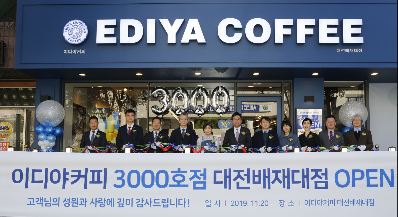Ediya Coffee CEO Moon Chang-gi (sixth from left) and the franchise owner of the 3,000th store in Daejeon (fifth from left) pose for a photo during an opening ceremony held in Daejeon, Wednesday. (Ediya Coffee)