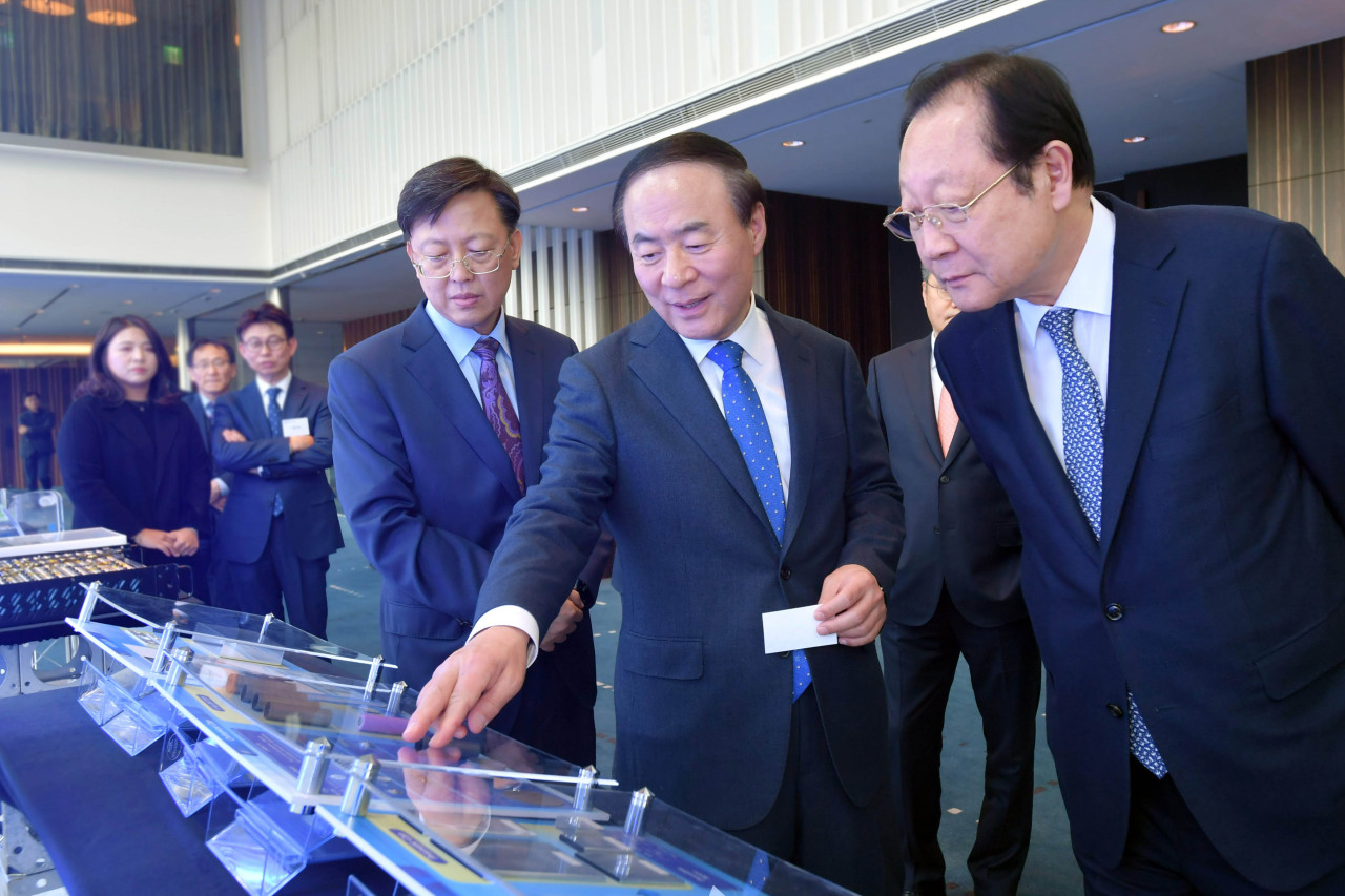 Samsung SDI CEO Jun Young-hyun (middle) introduces battery components to Kwon Ki-hong, chairman of Korea Commission for Corporate Partnership, at Samsung SDI Co-Growth Day held in Suwon, Gyeonggi Province, on Tuesday. (Samsung SDI)