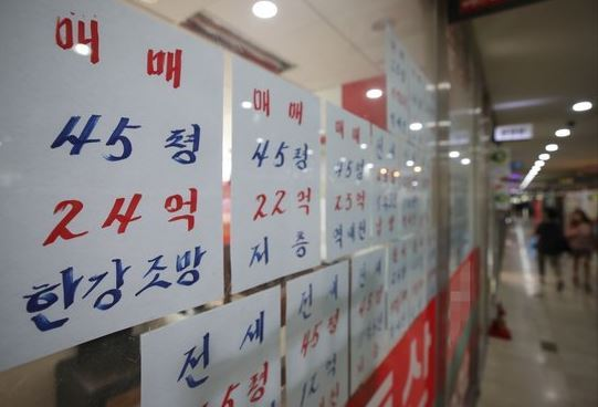 Information on prices of apartment units, put up for sale, are posted on the window of a real-estate agent office in Seoul earlier this year. (Yonhap)