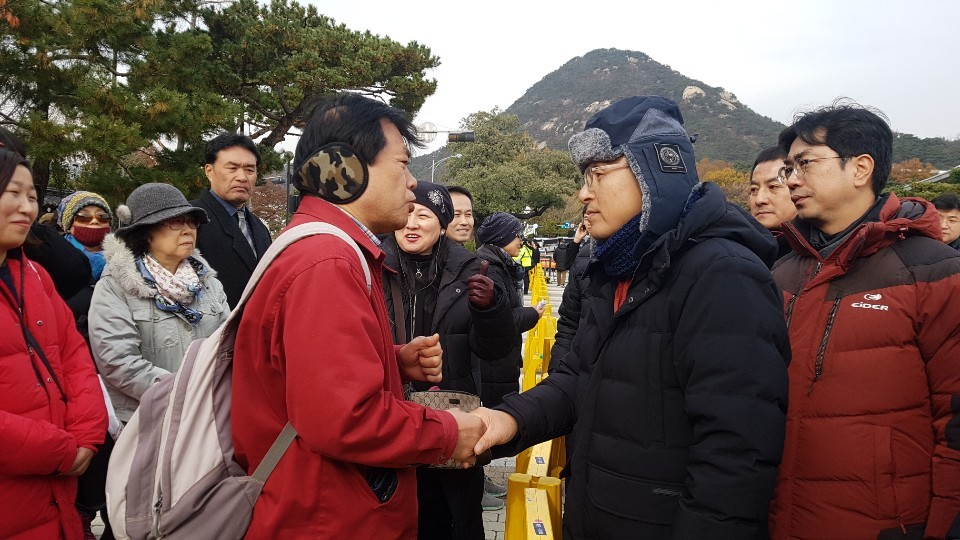 Chairman Hwang (right in black jacket) shaking hands with supporters on Thursday (Choi Si-young/The Korea Herald)