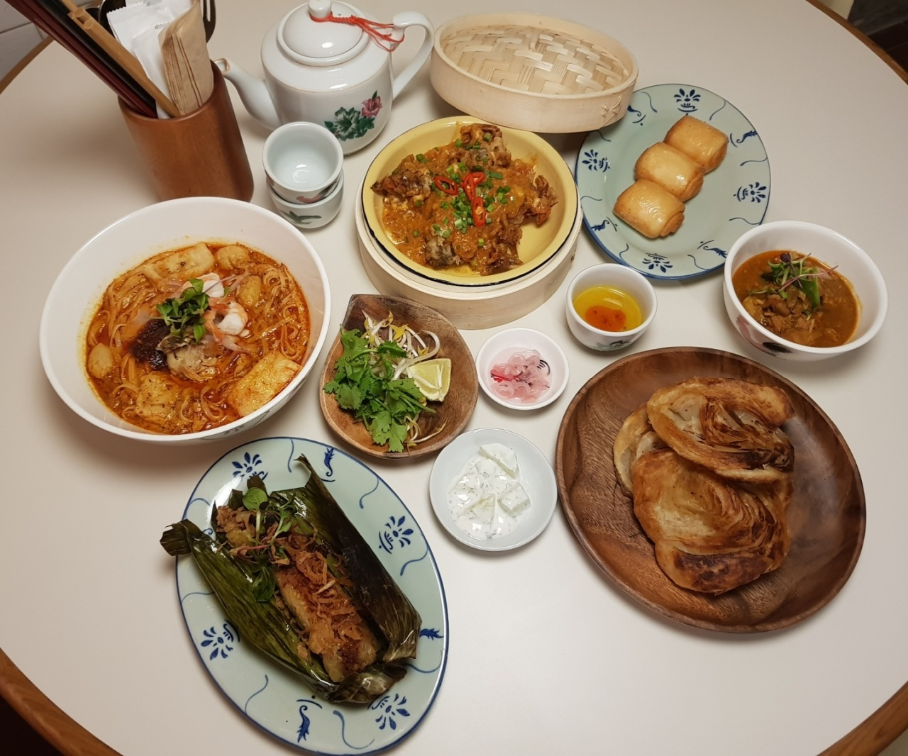 Clockwise from top left: Nyonya laksa, chili crab with fried mantou buns, chicken curry and roti canai and pulut panggang (Choi Ji-won/The Korea Herald)