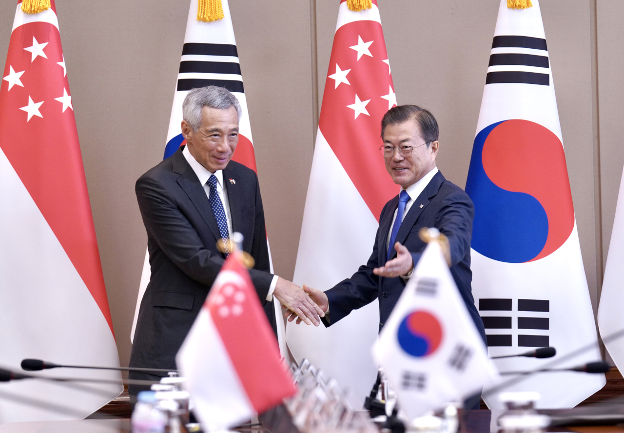 President Moon Jae-in shakes hands with Singapore's Prime Minister Lee Hsien Loong at Cheong Wa Dae on Saturday, ahead of the upcoming ASEAN summit to be held in Busan next week. (Yonhap)