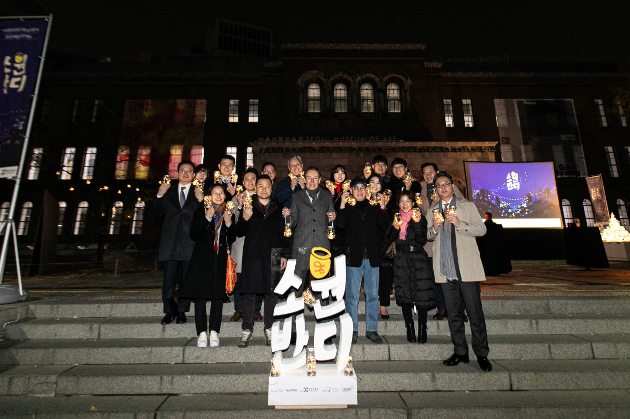 Han Sung Motor CEO Ulf Ausprung (fourth from right, front row) poses with Seoul Foundation for Arts and Culture and Han Sung Motors employees during a lantern-lighting ceremony held at Deoksugung in Seoul on Thursday. (Han Sung Motors)
