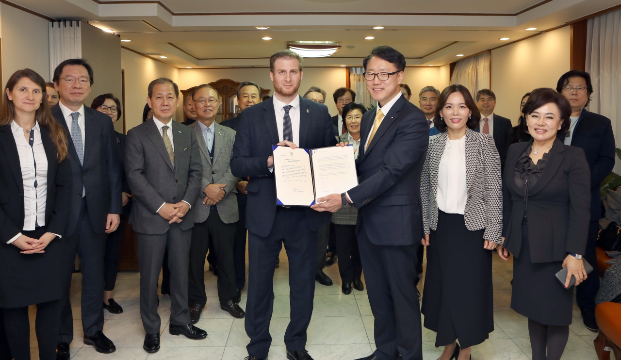 Hungarian Ambassador to Korea Mozes Csoma (left) and Ryu Kwon-ha hold a letter of appointment at a ceremony at the Hungarian Embassy in Seoul on Friday. (Foreign Language Newspapers Association of Korea)