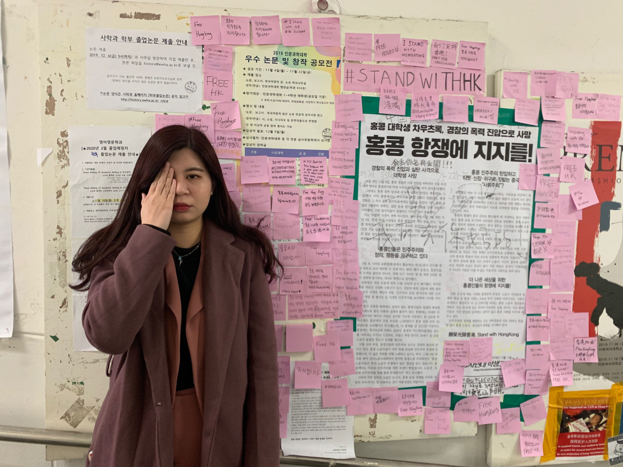 An international student from Hong Kong, poses in front of the Ewha Womans University wall covered with posters and sticky notes expressing support for Hong Kong protests. (Kim Arin/The Korea Herald)