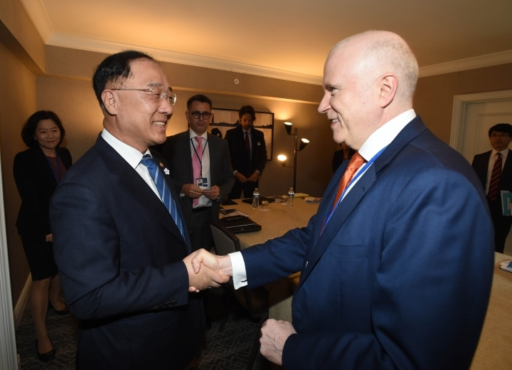 Deputy Prime Minister and Finance Minister Hong Nam-ki (left) shakes hands with James McCormack, managing director and global head of sovereign and supranational ratings at Fitch, ahead of the annual meeting in Washington in October. (Ministry of Economy and Finance)