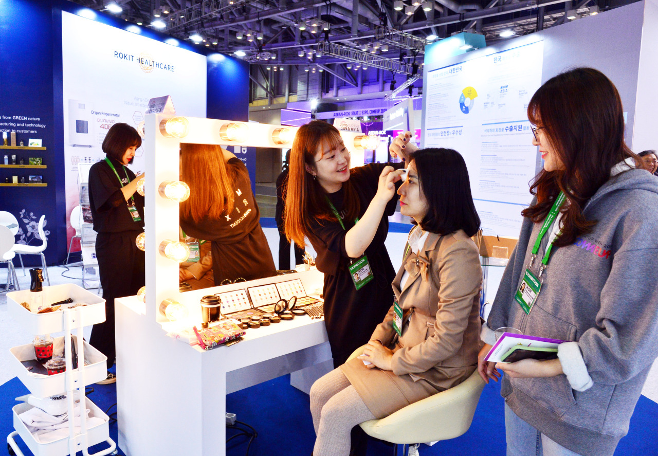 A visitor at the K-beauty Festival receives makeup at BEXCO on Monday. (Park Hyun-koo / The Korea Herald)