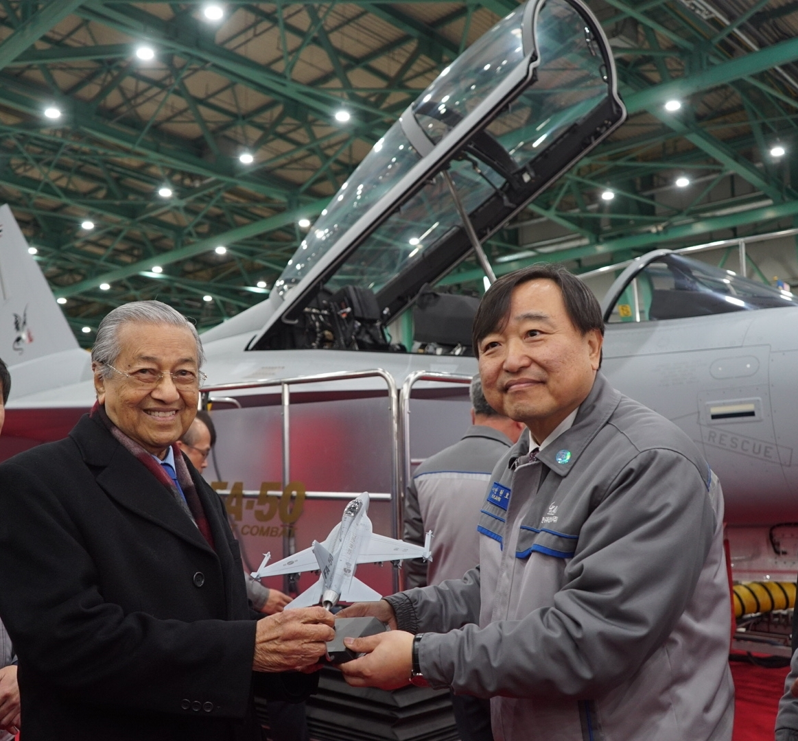 Caption: KAI CEO Ahn Hyun-ho (right) gives a model of FA-50 to Malaysian Prime Minister Mahathir Mohamad at KAI's aircraft production site on Monday. (KAI)