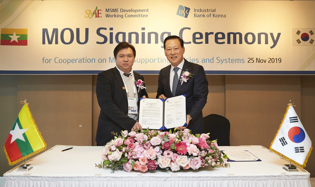 Kim Do-jin (right), CEO of Industrial Bank of Korea, and Dr. Min Ye Paing Hein, deputy minister for the Ministry of Industry of the Republic of the Union of Myanmar,pose for a photograph Monday at Lotte Hotel Busan, after signing a memorandum of understanding on SME development. (IBK)