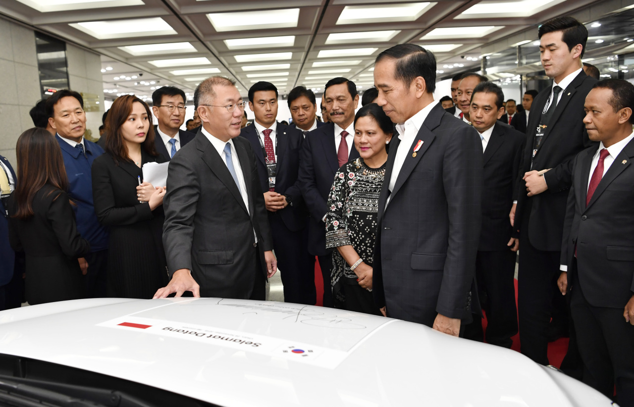 President of Indonesia Joko Widodo (center right) and Executive Vice Chairman of Hyundai Motor Group Chung Euisun (center left) chat in front of Kona Electric after leaving a signature on the car, prior to the investment clinch ceremony which took place at the automaker's plant in Ulsan, Tuesday. (Hyundai Motor Group)