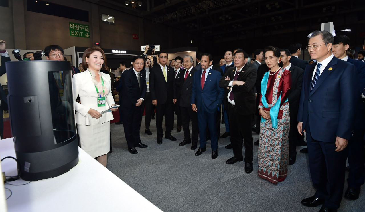 Including South Korean President Moon Jae-in (right), the leaders of ASEAN countries look at GiGA Genie hologram service at KT's booth at BEXCO in Busan on Tuesday. (KT)