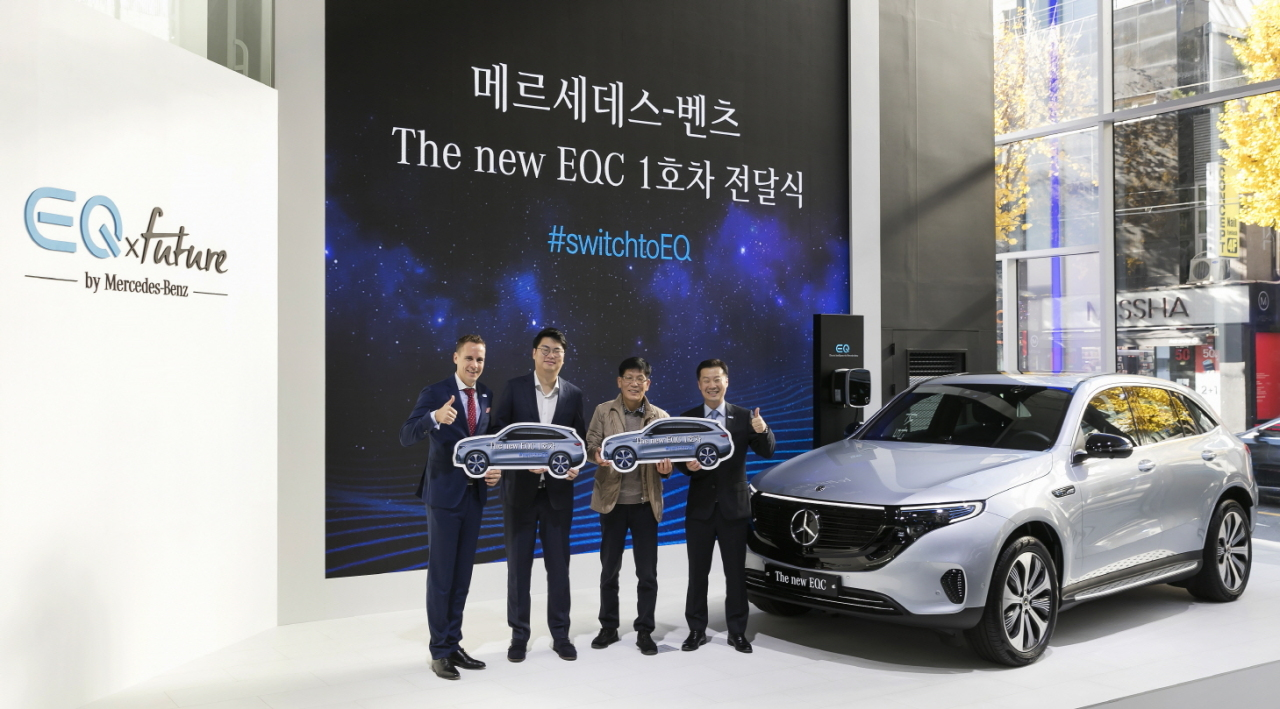 Mark Raine (far left), vice president of products and marketing at Mercedes-Benz Korea, and Lee Sang-kuk (far right), the company's vice president of sales, pose for a photo with the first customer to receive the new EQC, at the EQ Future Pavilion in Sinsa-dong, Seoul, Thursday. (Mercedes-Benz Korea)