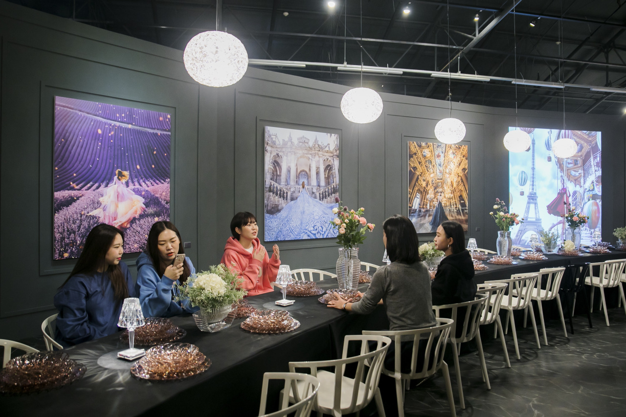 "Visitors sit at a table at The Black Plaza zone in ""Museum of Colors"" exhibition held at culture complex Sfactory in Seongsu-dong, eastern Seoul. (Sfactory)"