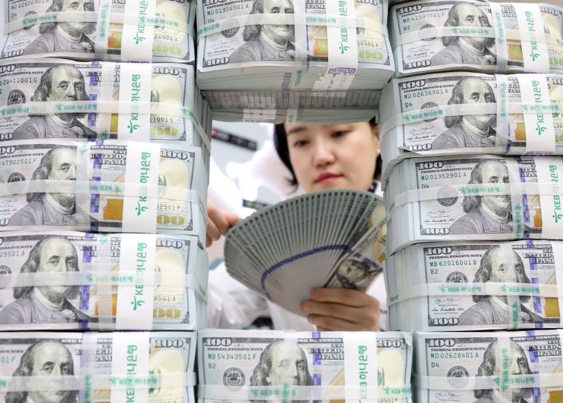 An employee at the headquarters of KEB Hana Bank in Seoul looks at US dollar notes to spot counterfeits. The greenback shows strong position against the Korean won this month. (Yonhap)