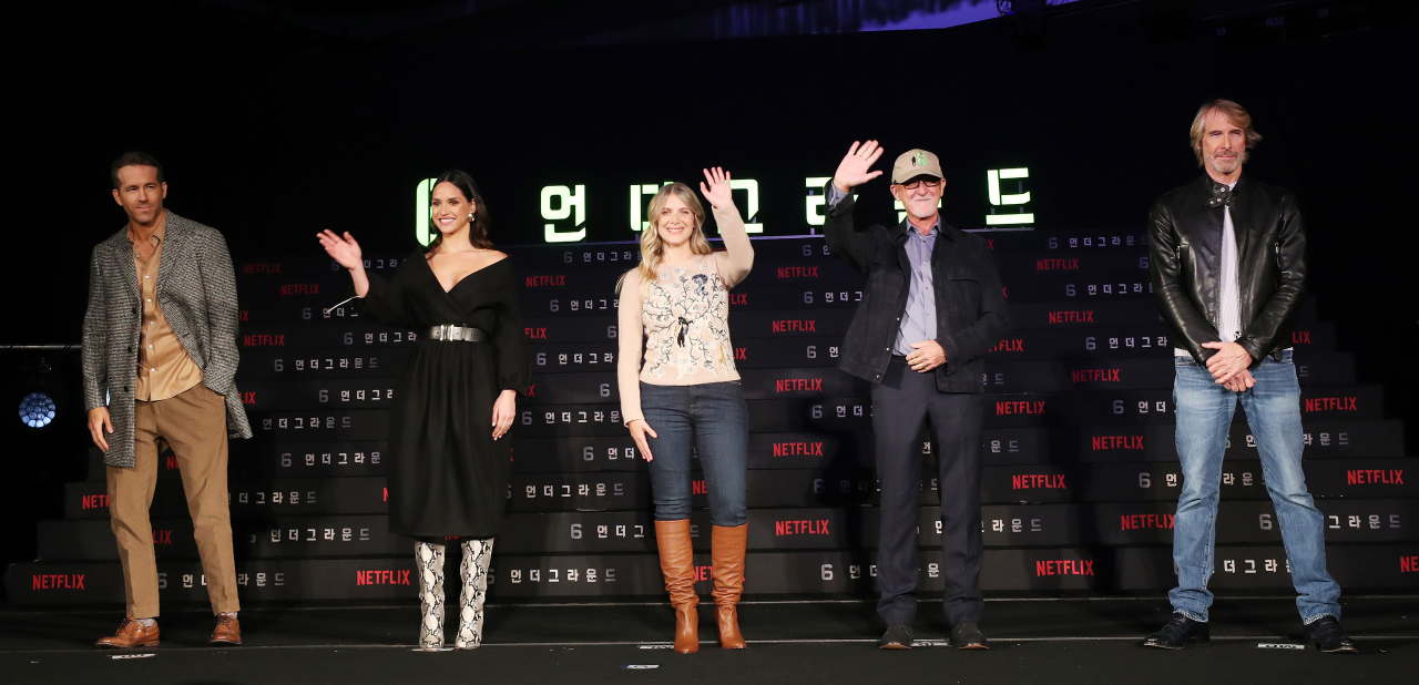 "Director Michael Bay (far right) and producer Ian Bryce (second from right) pose for a photo during a press conference in Seoul on Monday with the cast members of ""6 Underground."" From left: Ryan Reynolds, Melanie Laurent and Adria Arjona. (Yonhap)"