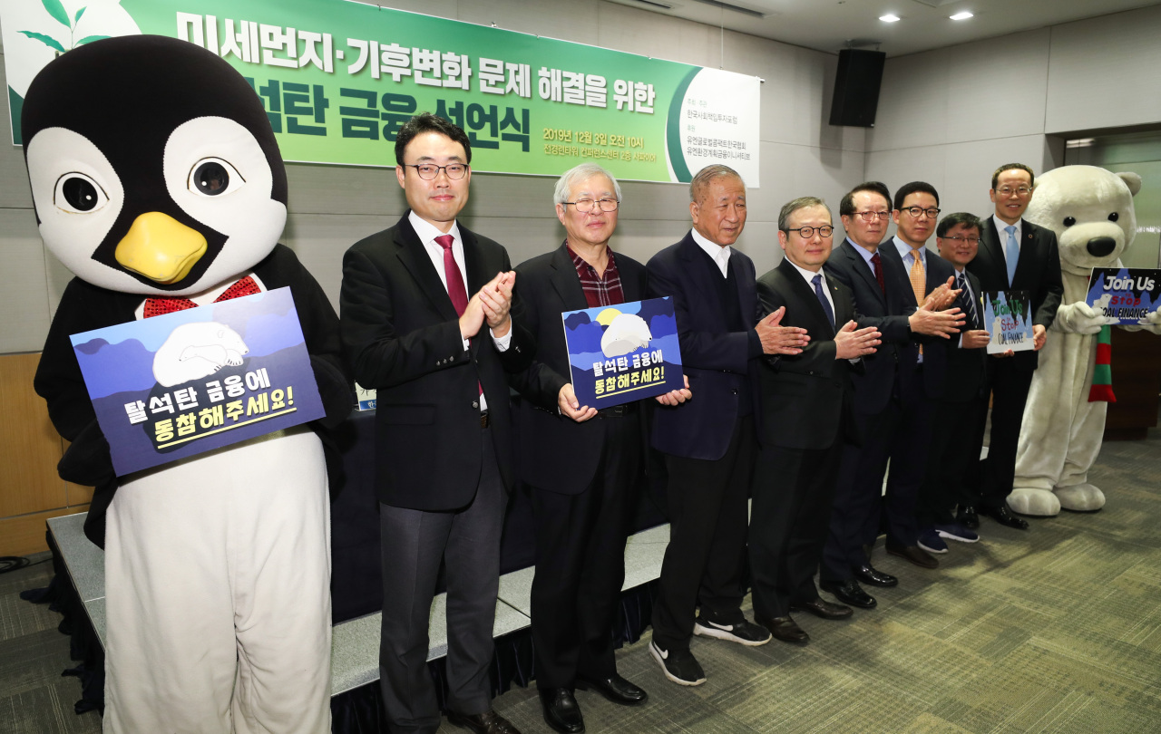 Executives from UN Environment Program, Korea Sustainability Investing Forum, DB Insurance, Korean Teachers' Credit Union and Public Officials Benefit Association pose for a photo during a ceremony to announce an end to coal project financing on Tuesday in Seoul. (Yonhap)