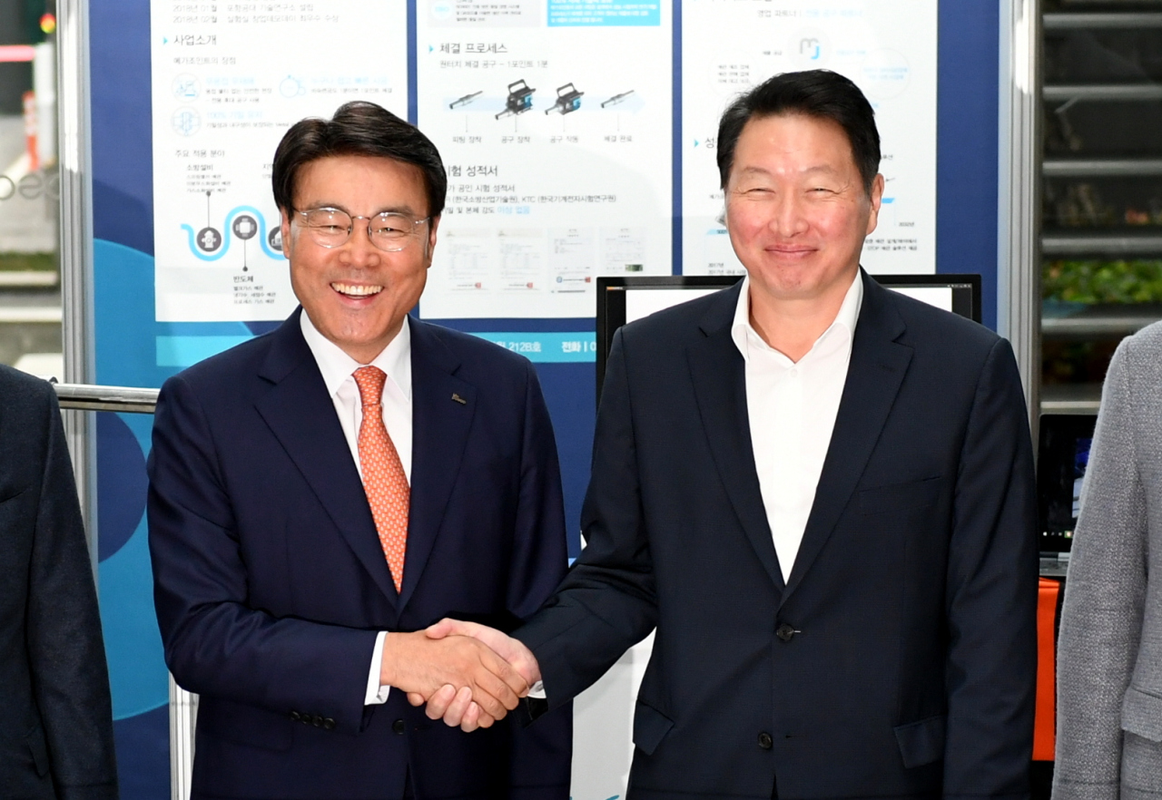 Posco Chairman Choi Jeong-woo (left) poses with SK Group Chairman Chey Tae-won for photo at Posco`s Seoul office on Tuesday. (Posco)