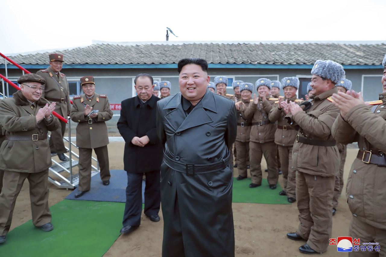 This undated file photo provided on Friday, Nov. 29, 2019, by the North Korean government, shows North Korean leader Kim Jong-un (center) surrounded by a military unit, reacts to what it claims as a test firing of its
