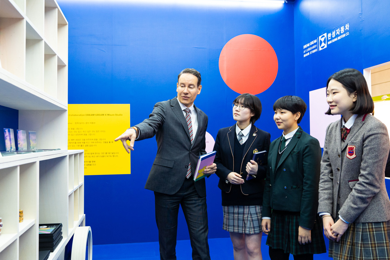 Han Sung Motor CEO Ulf Ausprung (left) and Dream Gream scholarship students look at goods at the 2019 Seoul Design Festival in Seoul. (Han Sung Motors)