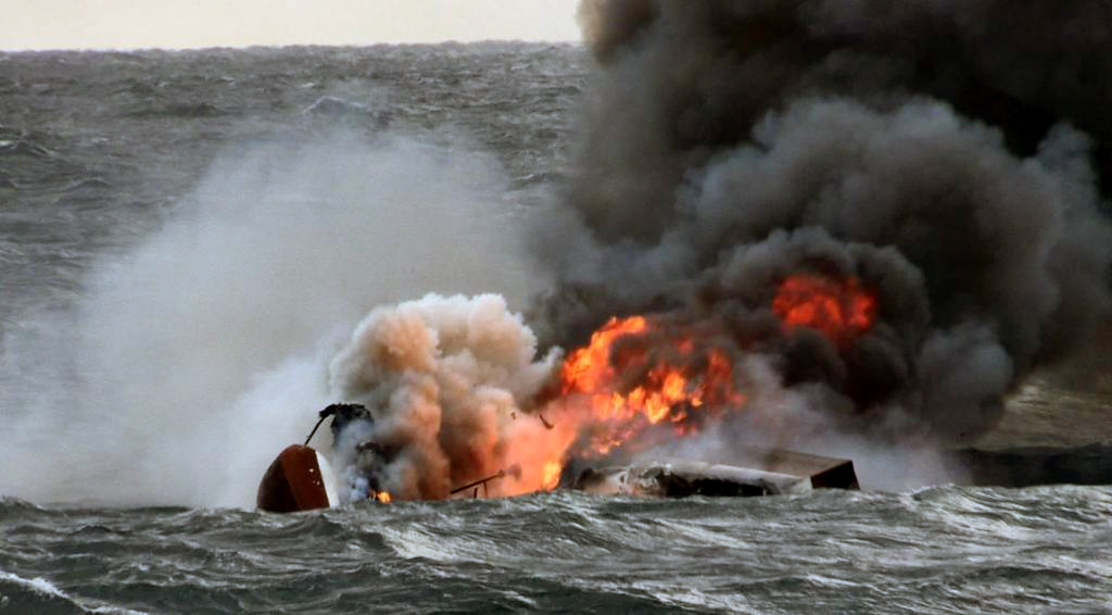 A capsized boat on fire is submerged in the waters near Jeju Island on Nov. 19. (Jeju Regional Coast Guard)
