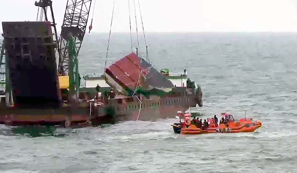 The rear part of the capsized boat is raised from the waters on Nov. 22. (Yonhap)