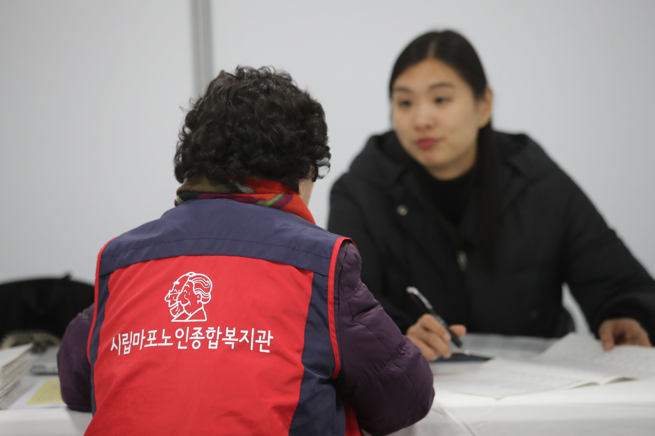 A senior citizen talks with a consultant at a job fair for the elderly in Seoul on Wednesday. (Yonhap)