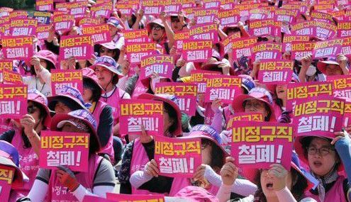 Nonregular employees working at schools stage a rally, demanding conversion of their status into regular employees in front of the headquarters of Busan City Office of Education in Yangjeong-dong, Busan, earlier this year. (Yonhap)