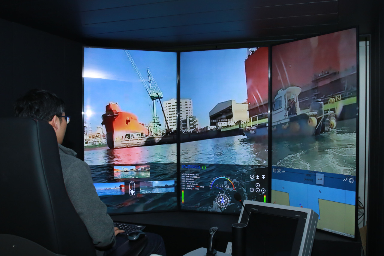 An engineer in Daejeon uses a 5G platform created by SK Telecom to remotely control a model vessel 250 kilometers away at Samsung Heavy's shipyard in Geoje, South Gyeongsang Province on Tuesday. (SK Telecom)