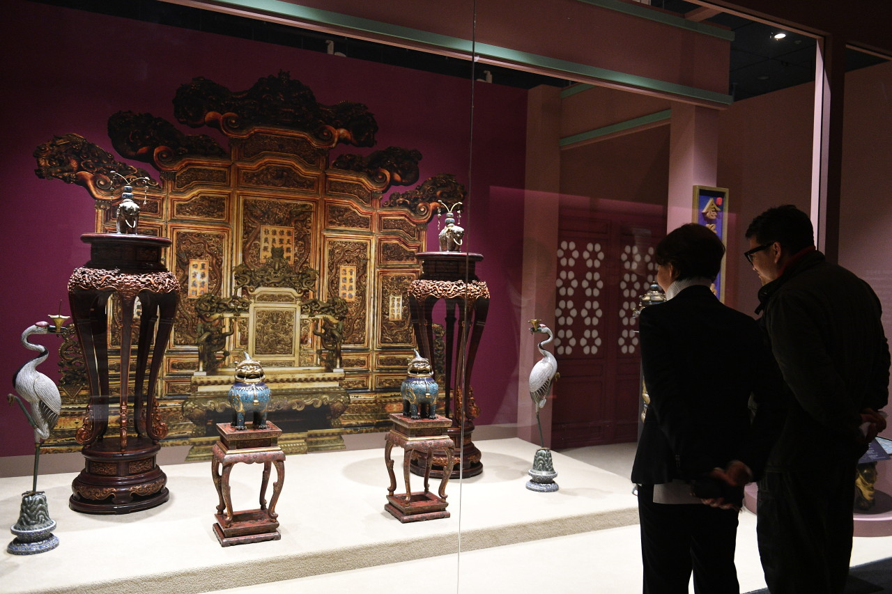 Visitors view a set of treasures and relics on display in a setting that resembles the interior of Chongzheng Hall, located at the center of Shenyang Palace. (National Palace Museum)