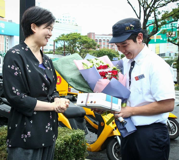 McDonanld's Korea Managing Director Melanie Cho (left) delivers flower and gifts to Lee Sung-min, a store manager of McDonald's Noyhung branch in Jeju. (McDonald's Korea)