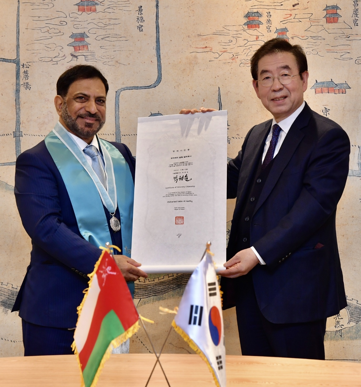 Omani Ambassador to South Korea Mohamed Al Harthy (left) receives honorary Seoul citizenship delivered by Seoul Mayor Park Won-soon at Seoul City Hall on Dec. 13. (Omani Embassy in Seoul)