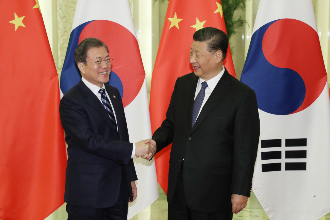 President Moon Jae-in and Chinese President Xi Jinping shake hands ahead of the summit meeting in Beijing on Monday. Yonhap
