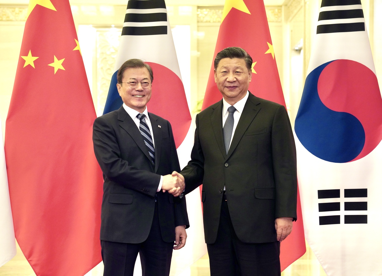 South Korean President Moon Jae-in (Left) shakes hands with Chinese President Xi Jinping in their summit at the Great Hall of the People in Beijing on Monday. (Yonhap)