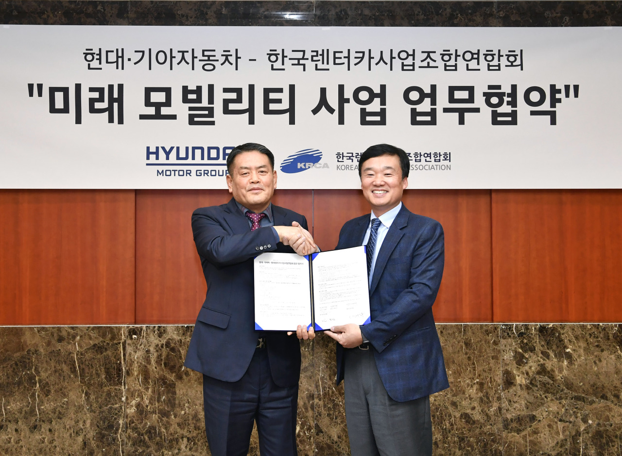 Hyundai Motor Group's open innovation business division chief Yoon Kyung-rim (right) and head of Korea Rental Car Business Association Cho Seok-tae shake hands after signing a memorandum of understanding Thursday. (Hyundai Motor Group)