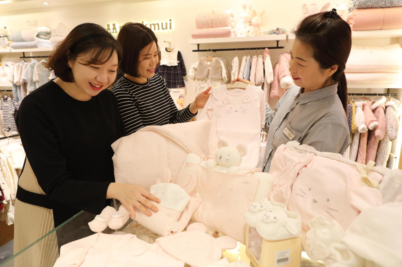 Shoppers look for white mouse-themed baby clothes at Lotte Department Store's headquarters in Sogong-dong, central Seoul on Wednesday. (Yonhap)