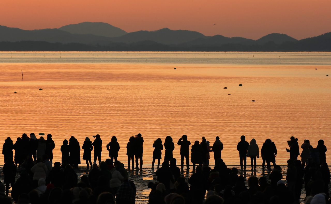 A crowd watches the sunrise from a beach in Gangneung, Gangwon Province, Wednesday. (Yonhap)