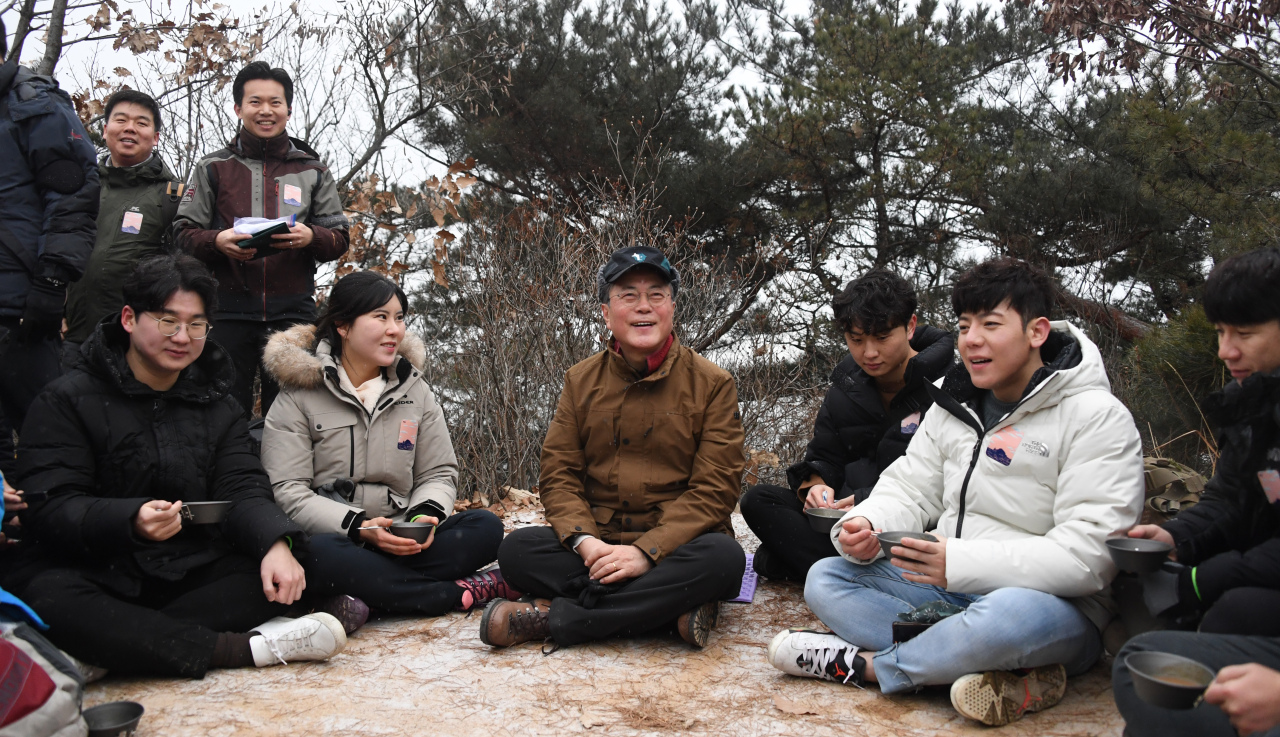 President Moon Jae-in (center) takes a break during a hike with citizens on Wednesday at Achasan in eastern Seoul. (Yonhap)