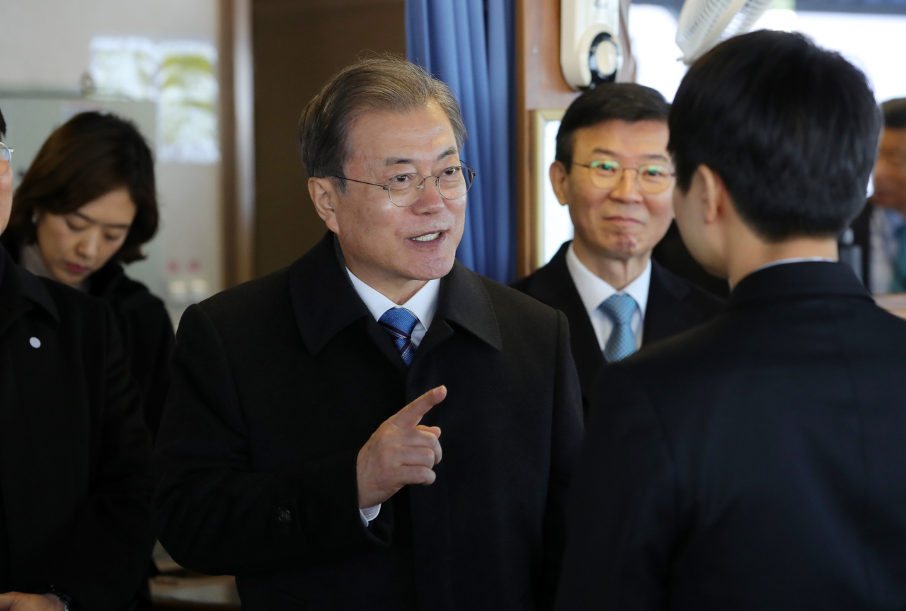 President Moon Jae-in speaks with the captain of the automobile carrier at the Pyeongtaek-Dangjin port on Friday. Yonhap