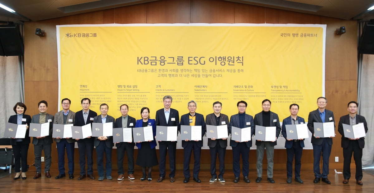 KB Financial Group Chairman Yoon Jong-kyoo (seventh from right) takes a group photo with his employees in front of a board stating ESG values at a New Year's event held in Yongin, Gyeonggi Province, on Friday. (KB Financial)