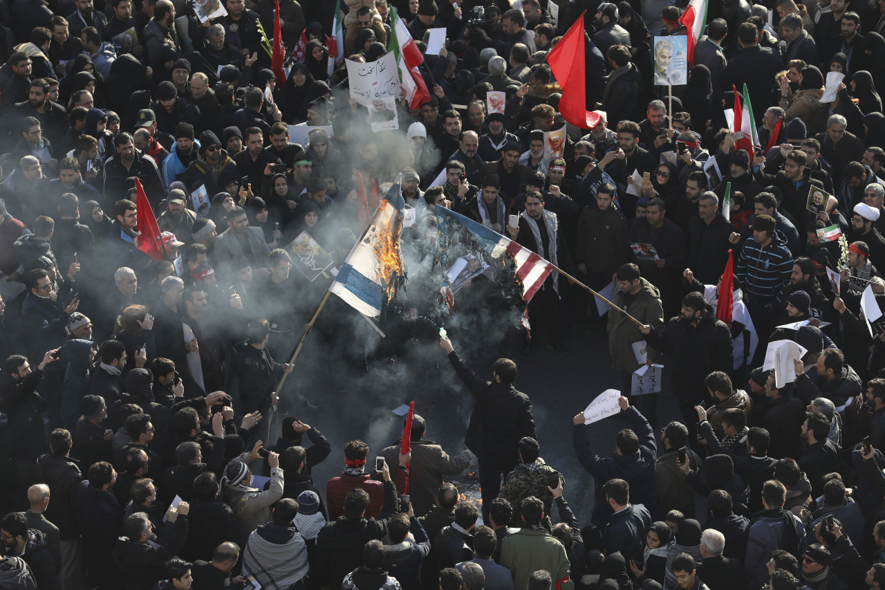 Mourners burn mock flags of the US and Israel during a funeral ceremony for Iranian Gen. Qassem Soleimani and his comrades, who were killed in Iraq in a US drone strike on Friday, at the Enqelab-e-Eslami (Islamic Revolution) square in Tehran, Iran, Monday. (AP-Yonhap)