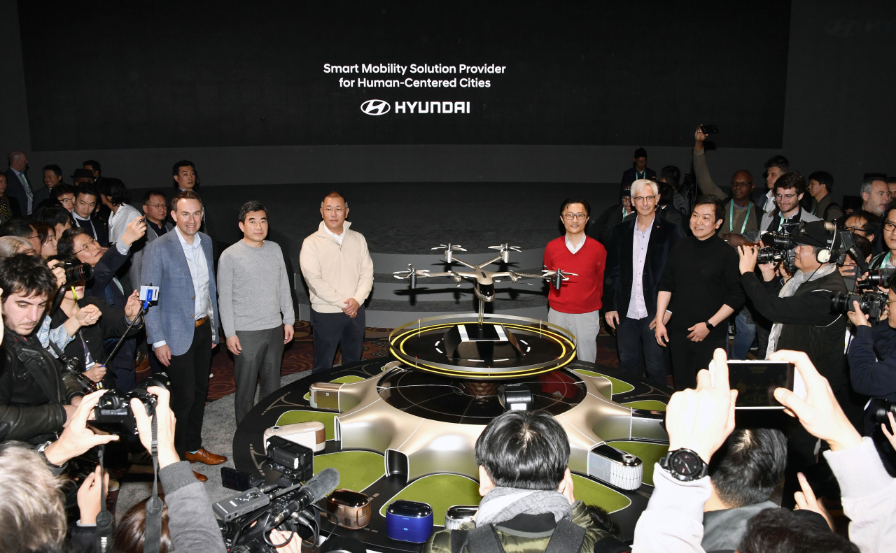 From left: Uber Elevate Chief Eric Allison, Hyundai Motor Group UAM business division head Shin Jae-won, Hyundai Motor Group Executive Vice Chairman Chung Euisun, Hyundai Motor Group strategic technology division president Chi Young-cho, Texas University's professor of psychology Art Markman, Hyundai Motor Design Center Head Lee Sang-yeob pose with PAV concept S-A1, PBV concept S-Link and hub concept S-Hub during Consumer Electronics Show 2020 in Las Vegas, Monday. (Hyundai Motor Group)