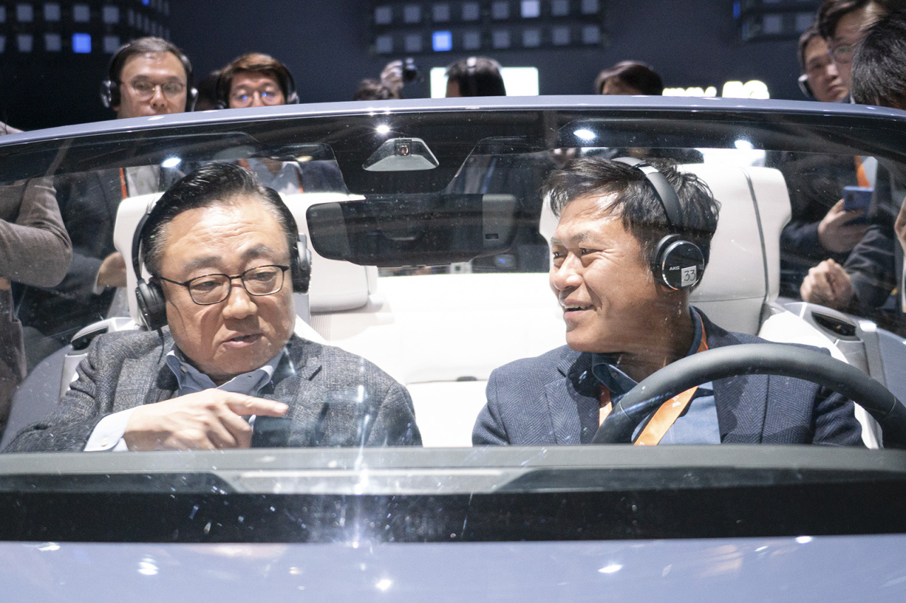 Koh Dong-jin (left), Samsung Electronics IT and mobile communications CEO, and Park Jung-ho, SK Telecom CEO, test-ride a newly developed digital cockpit, co-designed by Samsung Electronics and Harman International, at Samsung's CES 2020 booth at the Las Vegas Convention Center on Tuesday. (Yonhap)