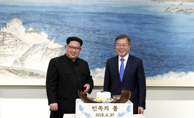 North Korean leader Kim Jong-un (left) and South Korean President Moon Jae-in smile after breaking open a chocolate dome together while dessert is being served during a dinner event following the inter-Korean summit in Panmumjeom in April, 2018. (Yonhap)