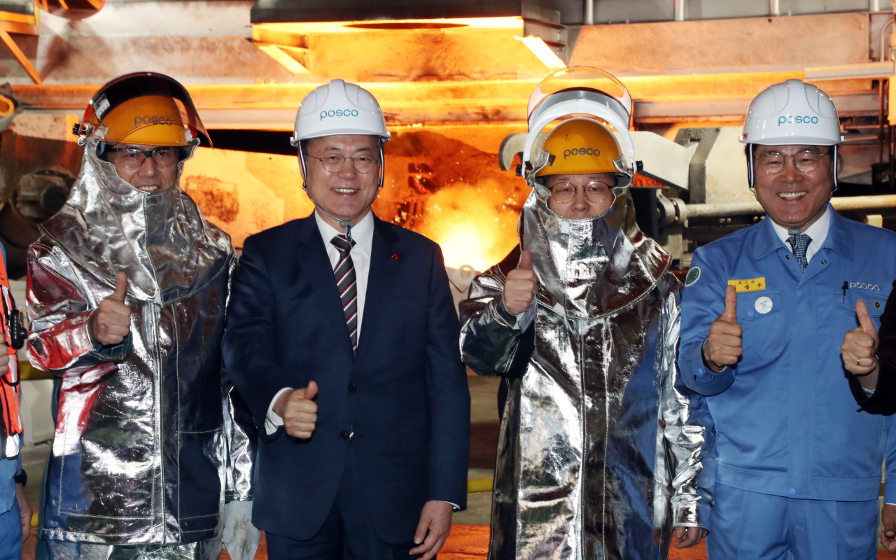 President Moon Jae-in (second from left) poses for a photo with Posco Chairman Choi Jeong-woo (right) and employees at one of Posco's steel mills in Pohang, North Gyeongsang Province, on Thursday. (Yonhap)