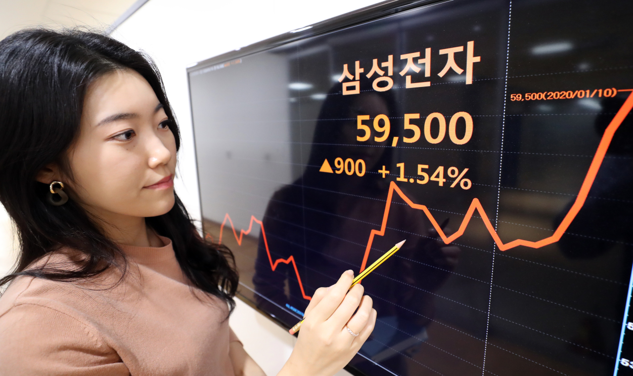 A Yonhap Infomax employee points to a screen showing Samsung Electronics' share price, Friday. (Yonhap)