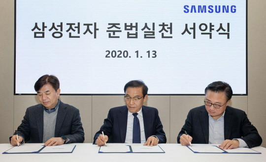 Samsung Electronics' chief executives, Kim Hyun-seok (from left), Kim Ki-nam and Koh Dong-jin, sign a pledge of compliance at an event held in Samsung Digital City in Suwon on Monday. (Samsung Electronics)