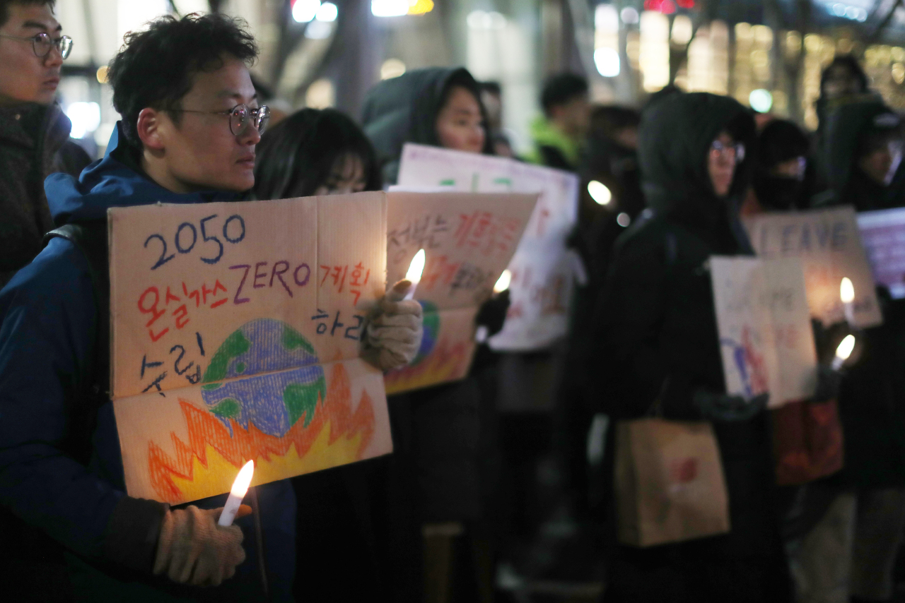 A man holds a handwritten sign at a rally in Gwanghwamun, central Seoul, on Monday to mourn the victims of Australia's bushfires. The sign's message is a call for the Korean government to achieve zero greenhouse gas emissions by 2050. (Yonhap)